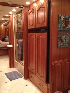The fridge is opposite my cooktop. There is a sliding pocket door between the shower door and the refrigerator door. There is another sliding pocket door in the back between our bedroom and my sink area.