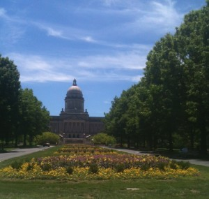 The Capitol Building is surrounded by a large landscape of lush lawns, big trees and beautiful flower beds.