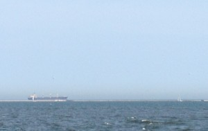 A cargo ship and a sailboat heading out to Lake Michigan.
