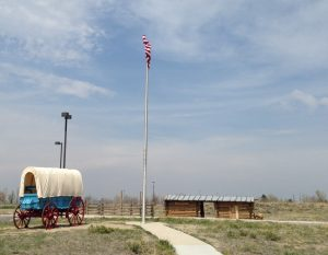 A covered wagon and a Pony Express Station outside the National Historic Trails Interpretive Center.